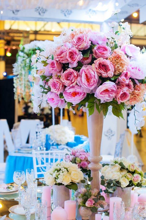 Mooi boeket van bloemen bij de huwelijkslijst in een restaurantdecor stock afbeelding