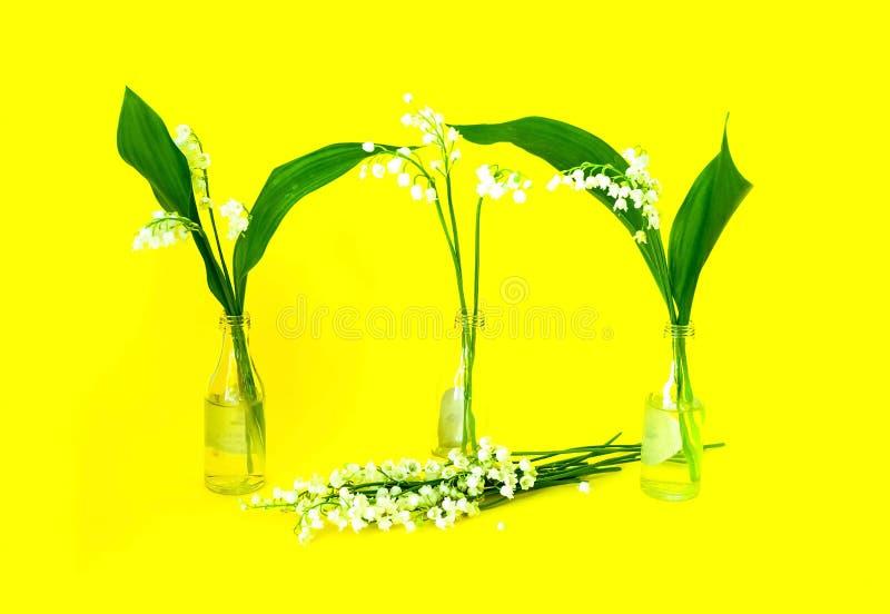 Mooi boeket van bloemenlelietje-van-dalen in weinig glasflessen op heldere gele achtergrond Gelukkige Moederdag! kaartconcept stock fotografie