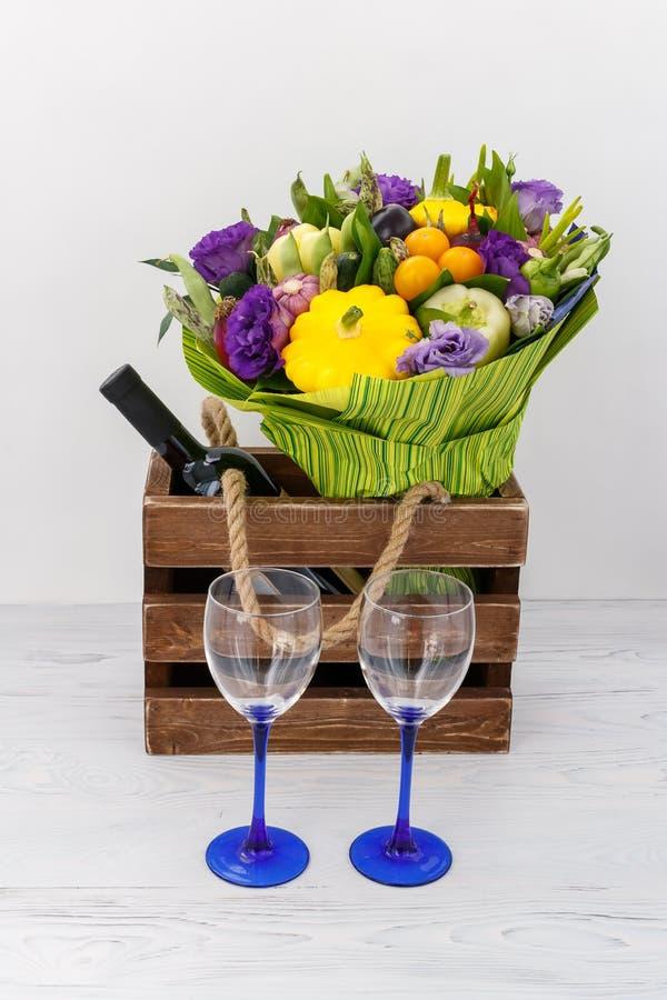 Mooi boeket van diverse groenten, een fles rode wijn en twee glazen op een witte achtergrond stock foto