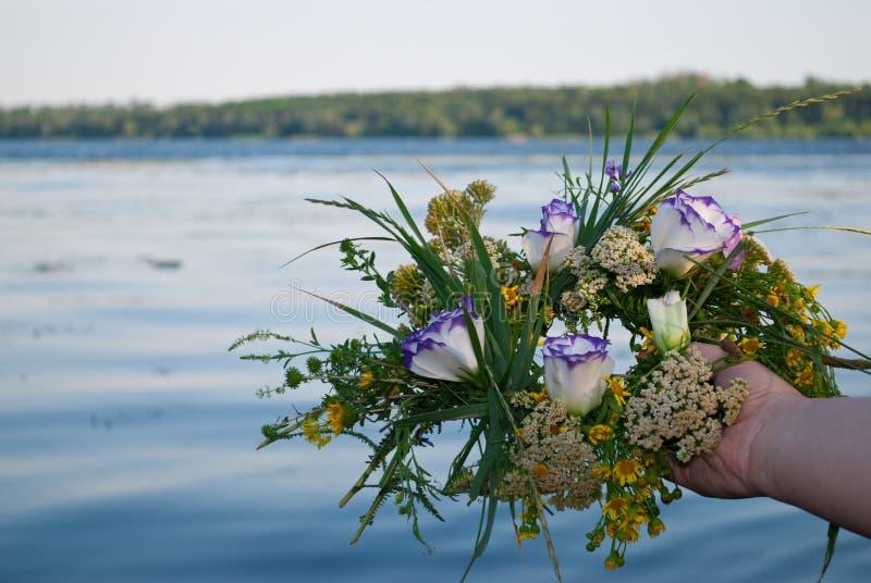 Mooi boeket van een kroon van wildflowers een meisje die een rivier over water houden stock afbeeldingen