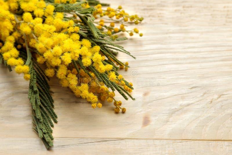 Mooi boeket van gele mimosabloemen op een natuurlijke houten lijst Vrije ruimte Ruimte voor tekst stock foto's