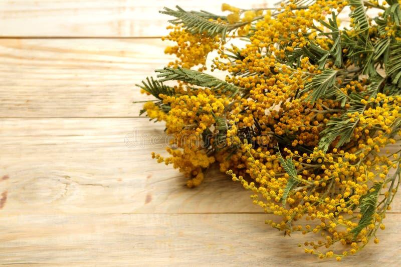 Mooi boeket van gele mimosabloemen op een natuurlijke houten lijst Vrije ruimte Ruimte voor tekst stock afbeelding