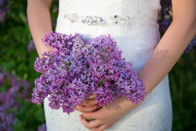 Mooi boeket van lilac bloemen in de handen van de bruid royalty-vrije stock afbeelding