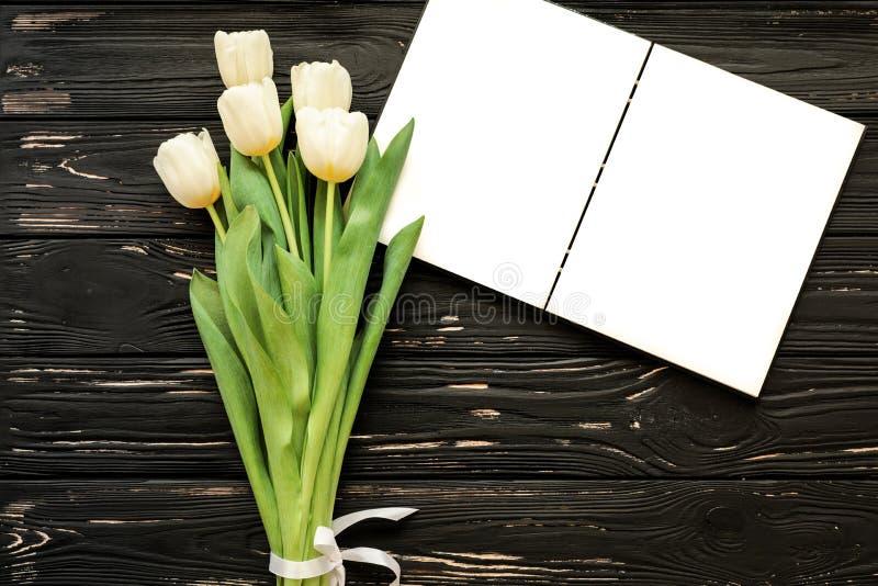 Mooi boeket van witte tulpen en open notitieboekje op de zwarte houten achtergrond royalty-vrije stock foto