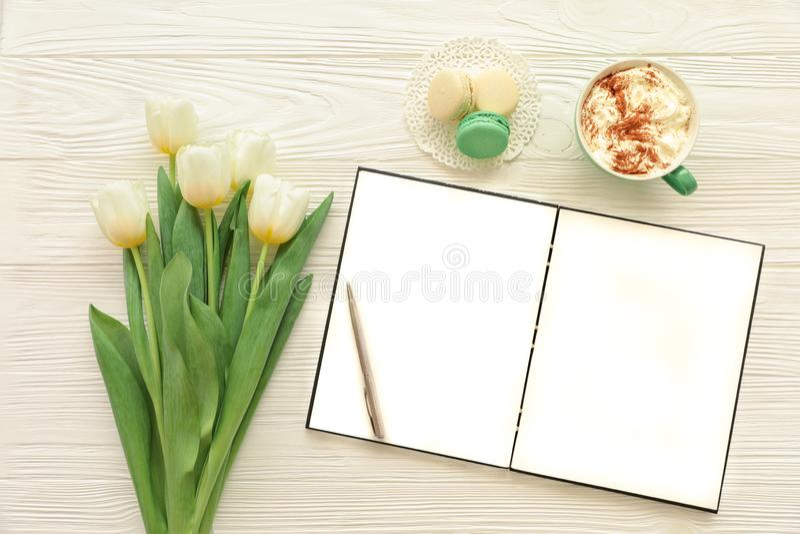 Mooi boeket van witte tulpen, leeg open notitieboekje, zilveren pen, kop van cappuccino, makaroons op de witte houten achtergrond stock foto