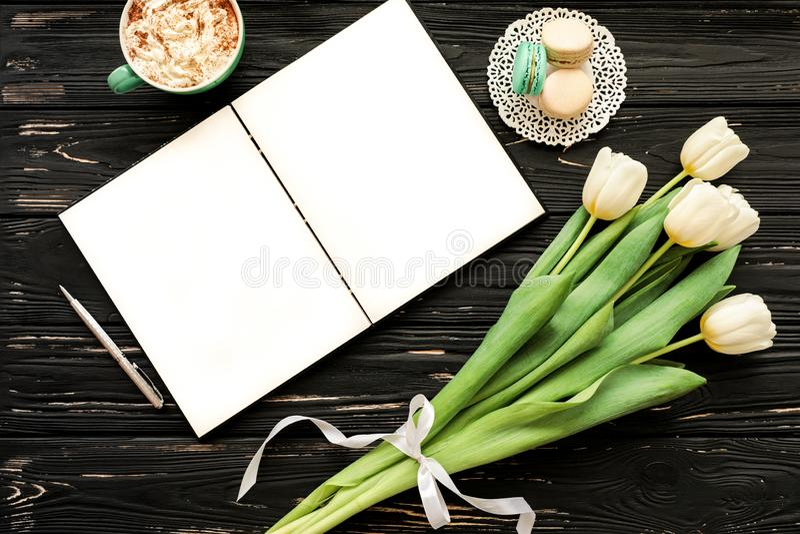 Mooi boeket van witte tulpen, leeg open notitieboekje, zilveren pen, kop van cappuccino, makaroons op de zwarte houten achtergron royalty-vrije stock afbeelding