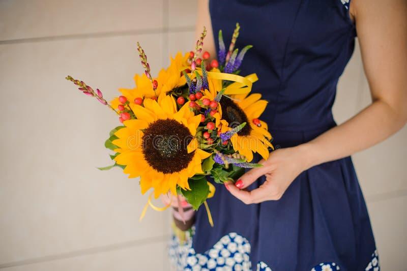 Mooi boeket van zonnebloemen in vrouwenhanden royalty-vrije stock afbeeldingen