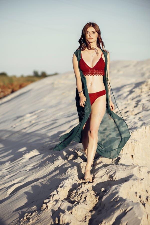 Mooi bohomeisje die in rood zwempak op zandig strand bij su lopen royalty-vrije stock foto's