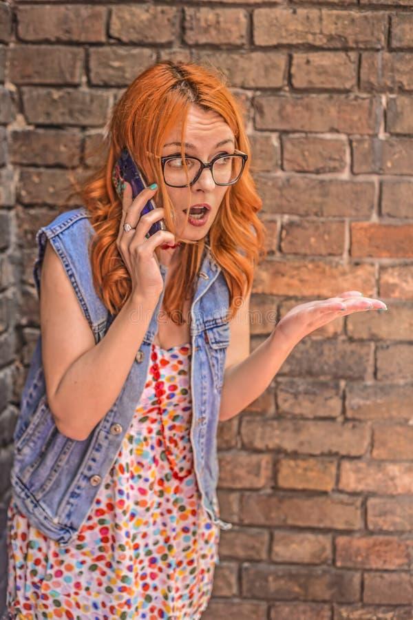 Mooi boos en verward roodharige Kaukasisch meisje die op slimme telefoon spreken royalty-vrije stock foto's