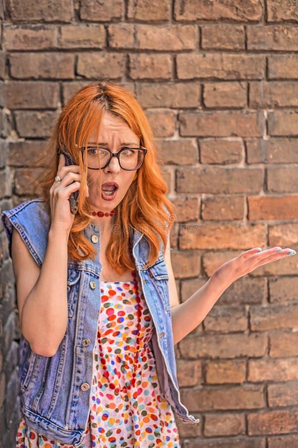 Mooi boos en verward roodharige Kaukasisch meisje die op slimme telefoon spreken stock afbeelding