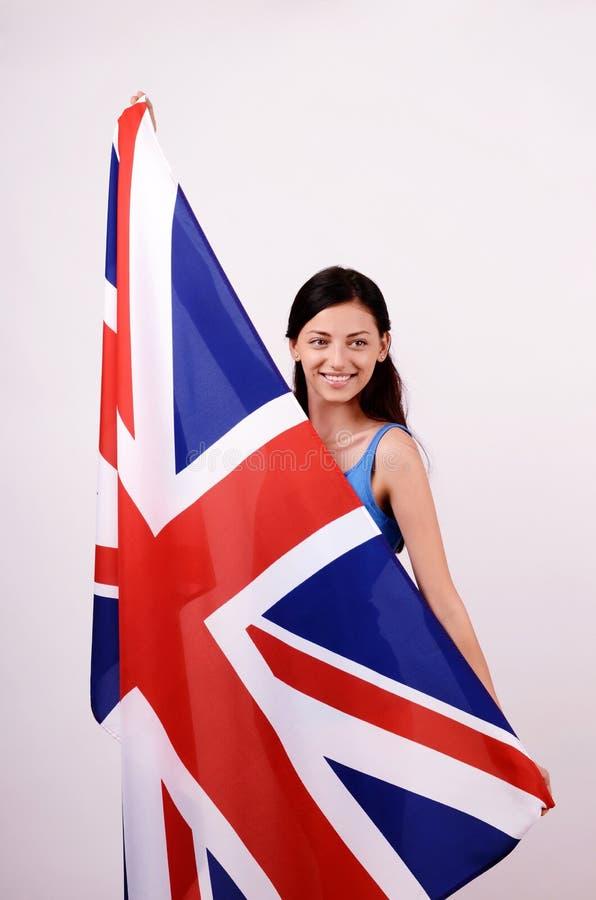 Mooi Brits meisje die steunend de Britse vlag die weg eruit zien glimlachen. royalty-vrije stock fotografie