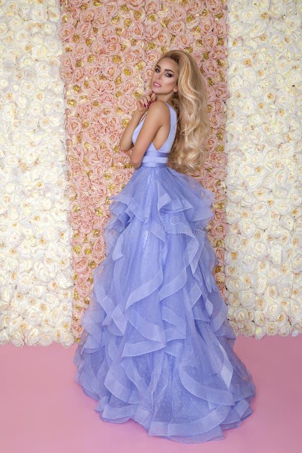 Mooi bruidmodel in blauwe verbazende huwelijkskleding Schoonheids jonge vrouw op de achtergrond van bloemen - Beeld stock afbeelding