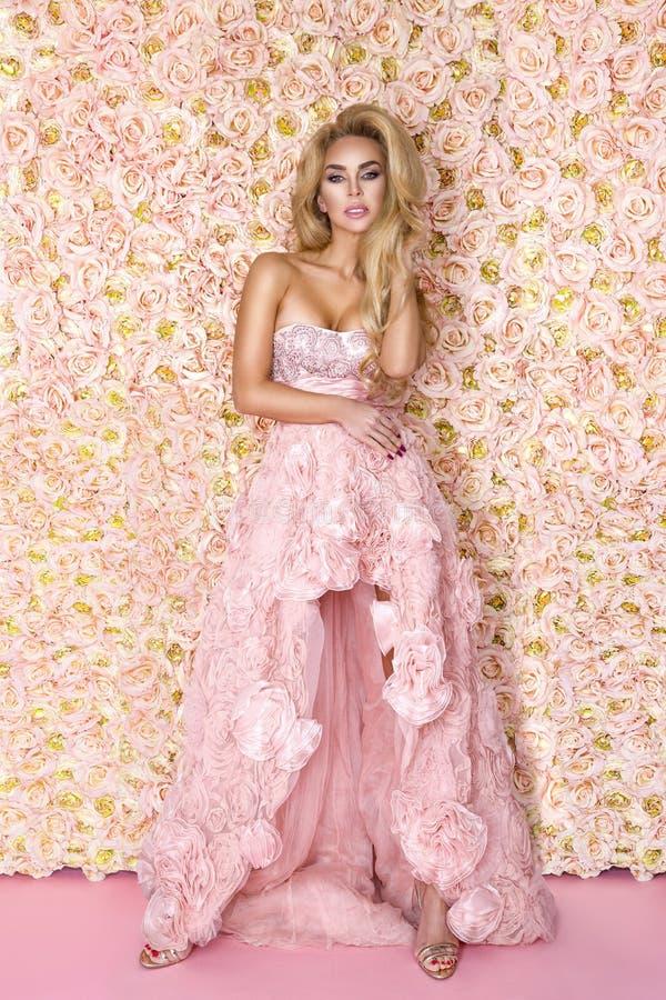 Mooi bruidmodel in roze verbazende huwelijkskleding Schoonheids jonge vrouw op de achtergrond van bloemen - Beeld royalty-vrije stock foto