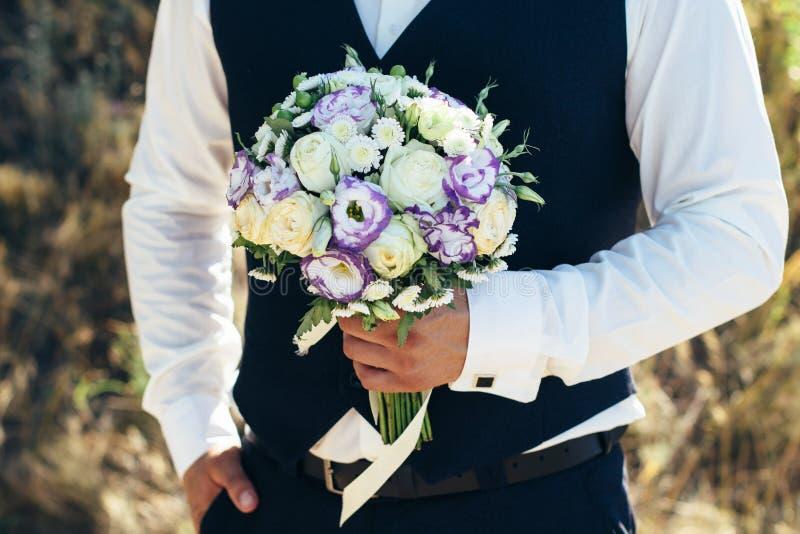 Mooi bruids boeket in handen van de bruidegom Huwelijksboeket van witte rozen, hypericum, lisianthus, chrysant, eustoma stock foto
