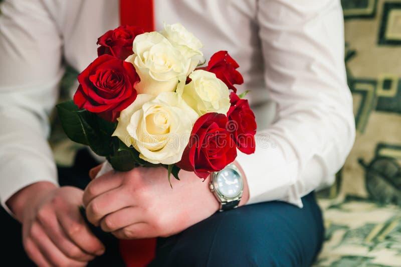 Mooi bruids boeket van witte en rode rozen in de handen van de bruidegom royalty-vrije stock afbeelding
