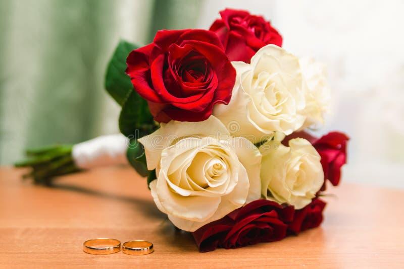 Mooi bruids boeket van witte en rode rozen en gouden trouwringen royalty-vrije stock foto's