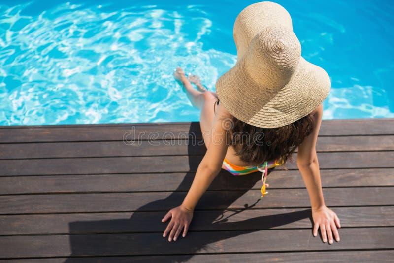Mooi brunette in bikinizitting door pool te paddelen stock foto's