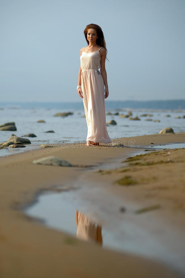 Mooi brunette in bleek - roze lange kleding stock afbeeldingen