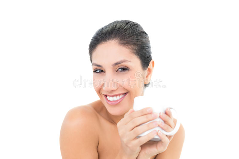 Mooi brunette die een witte mok houden en bij camera glimlachen stock foto's