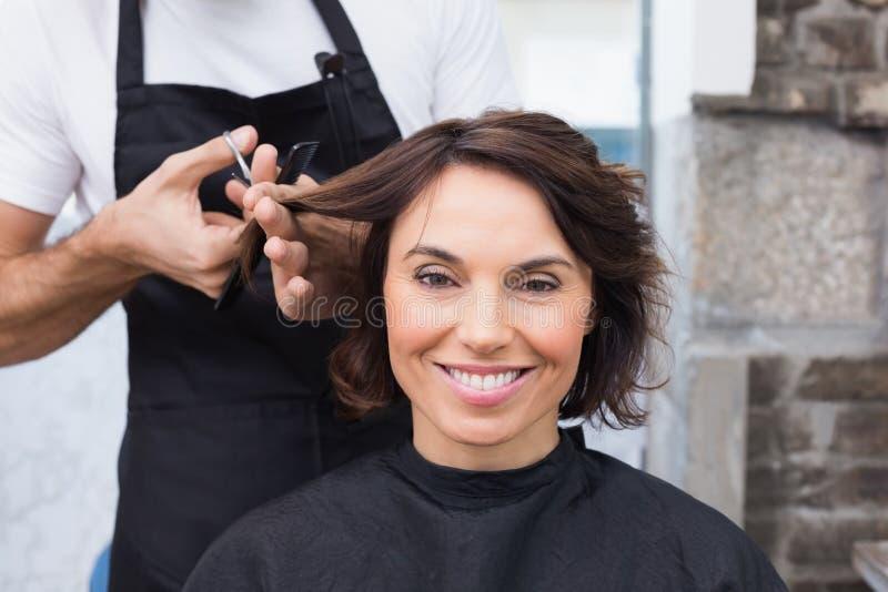 Mooi brunette die haar haarbesnoeiing krijgen stock fotografie