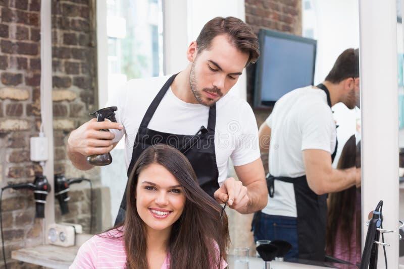 Mooi brunette die haar haarbesnoeiing krijgen stock foto
