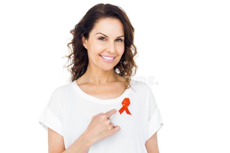 Mooi brunette die het rode lint van de hulpvoorlichting richten stock fotografie
