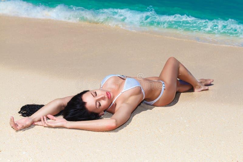 Mooi brunette die van de zon op de tropische kust genieten stock foto