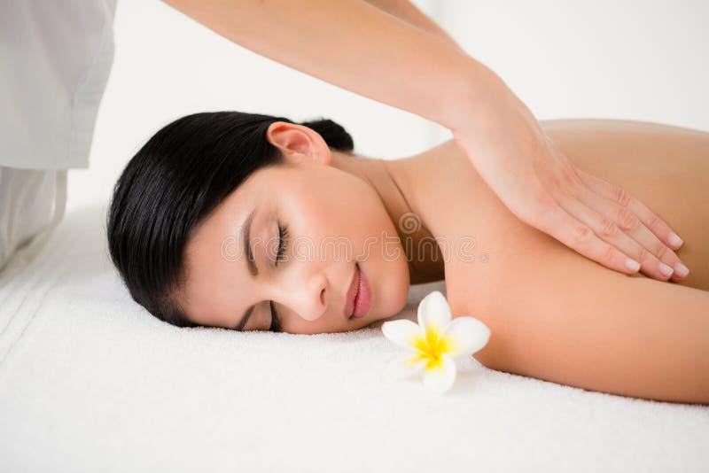 Mooi brunette die van een massage ruikende bloem genieten bij camera royalty-vrije stock afbeelding