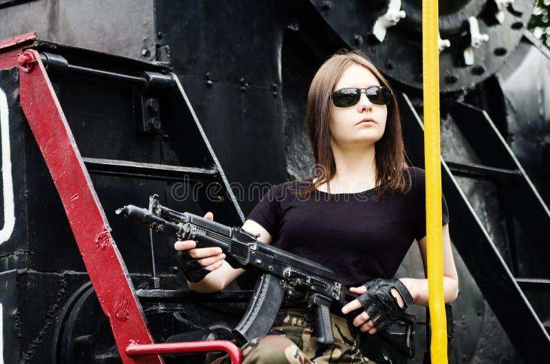 Mooi brunette in donkere glazen met een kanon royalty-vrije stock afbeelding