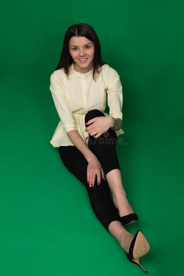 Mooi brunette in een gele blouse en zwarte broek op green stock afbeelding