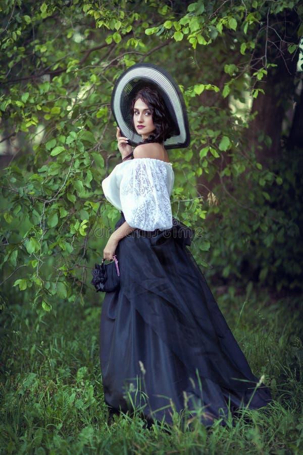 Mooi brunette in een grote zwart-witte hoed stock afbeeldingen