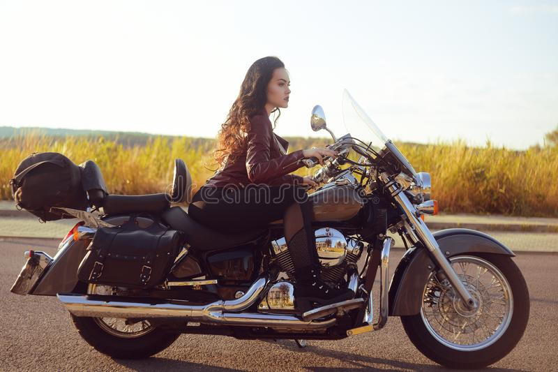 Mooi brunette in een rood leerjasje op een motorfiets op het gebied Meisje met mooi haar royalty-vrije stock foto