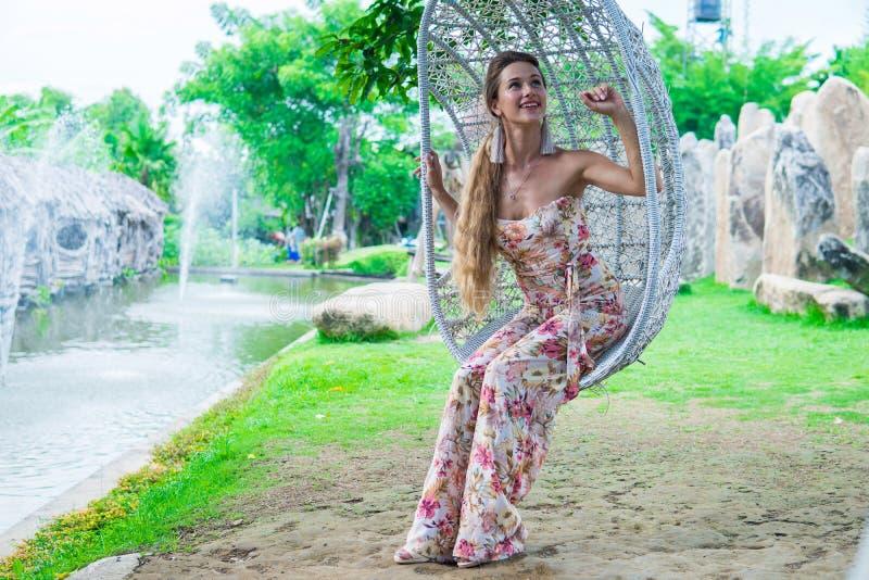 Mooi brunette in kleding die op een schommeling over het water in het Park in Zonnige dag slingert stock afbeelding