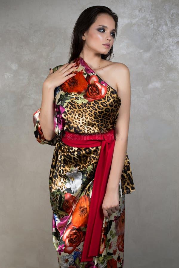 Mooi brunette met avondmake-up in een heldere drukkleding en een rode sjerp die zich op grijze achtergrond bevinden stock afbeelding