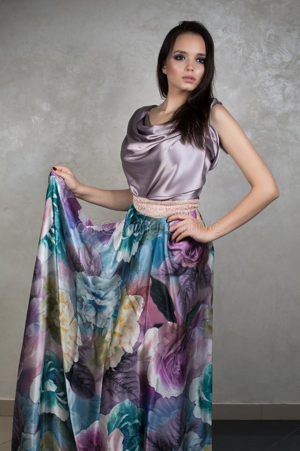 Mooi brunette met avondmake-up in purpere zijdekleding die zich op grijze achtergrond bevinden die handboord opheffen royalty-vrije stock afbeelding