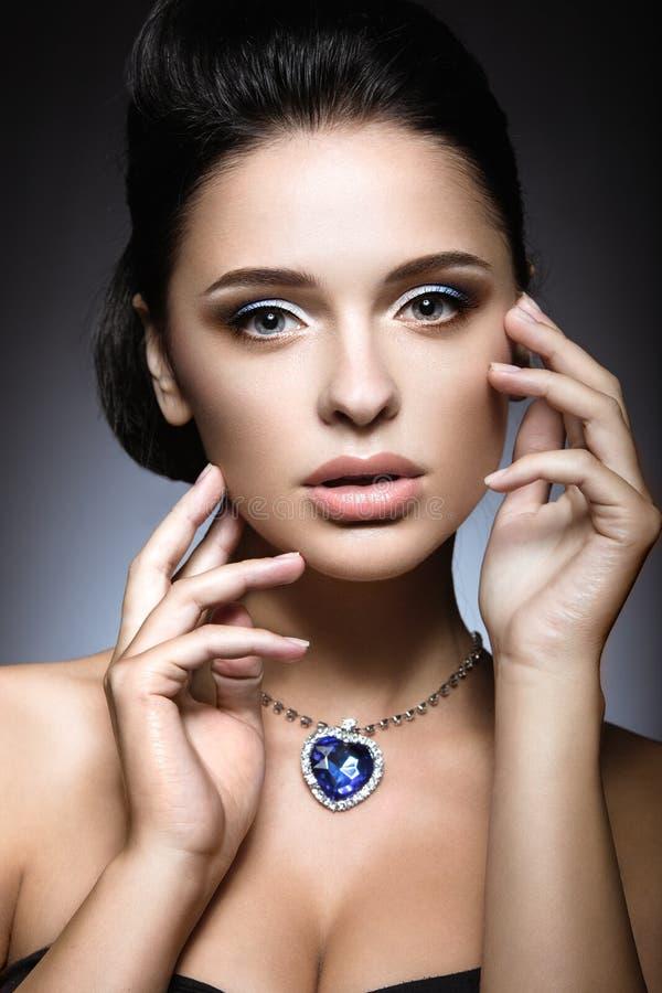 Mooi brunette met een heldere avondsamenstelling met een halsbandhart van de Oceaan royalty-vrije stock foto