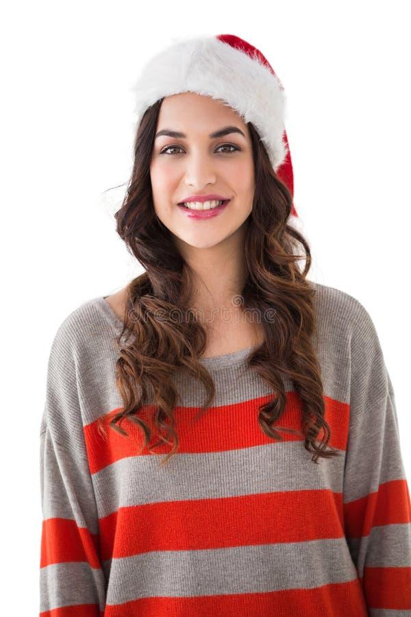 Mooi brunette in santahoed die bij camera glimlachen stock foto's