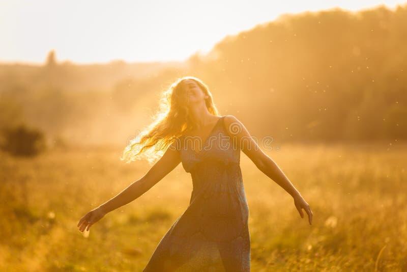 Mooi dansend meisje bij de zonsondergangzomer stock foto's