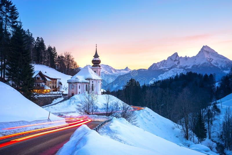 Mooi de berglandschap van het de wintersprookjesland in de Alpen met bedevaartkerk van Maria Gern en beroemde Watzmann-top in stock foto