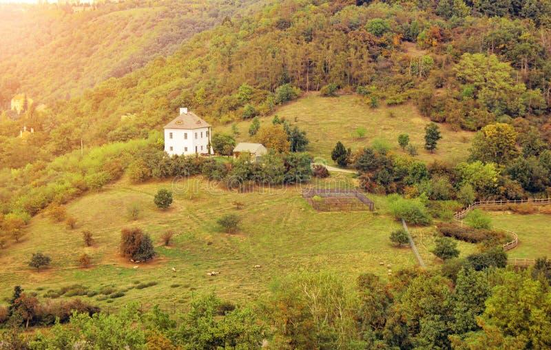 Mooi de herfstlandschap met traditioneel wit landbouwbedrijfhuis in gouden avondlicht royalty-vrije stock afbeelding