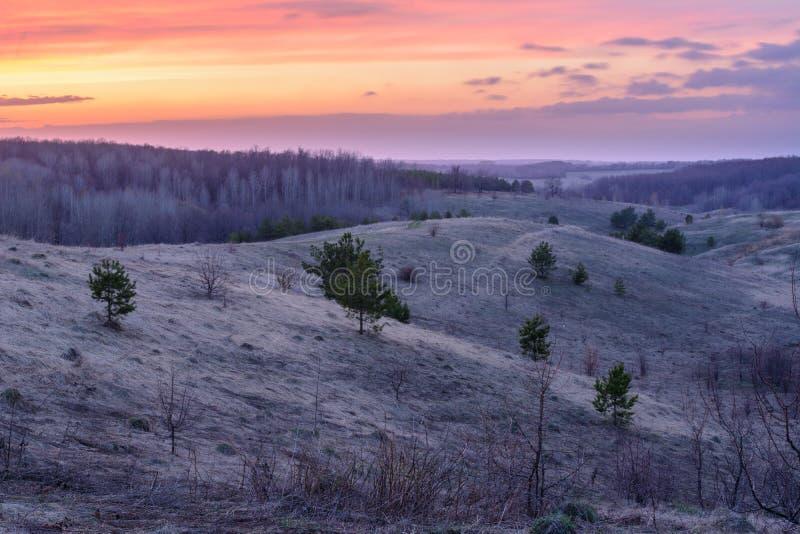 Mooi de lentelandschap: zonsondergang, bomen, bos, bergen, heuvels, gebieden, weiden en hemel Schitterende, rode hemel met zware  royalty-vrije stock foto's