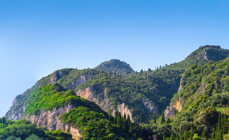 Mooi de zomer panoramisch landschap Cipresheuvels en groene berghellingen Ergens op Korfu Griekenland Middellandse Zee stock afbeeldingen