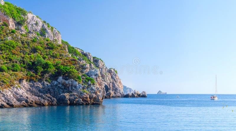 Mooi de zomer panoramisch zeegezicht Weergeven van de klip in de overzeese baai met glashelder azuurblauw water in zonneschijndag stock afbeelding
