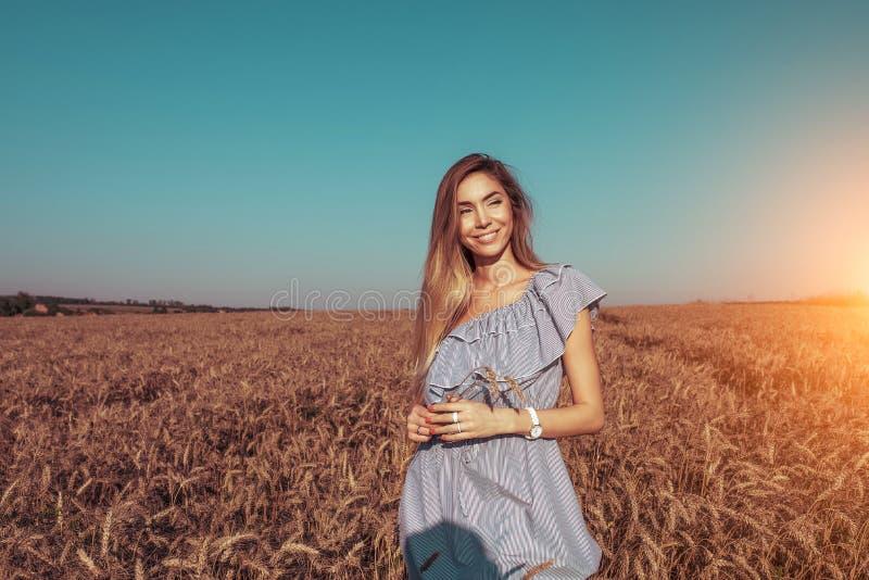 Mooi de zomermeisje op een tarwegebied, in een blauwe kleding, in haar oren van de handtarwe Gelukkige glimlachen, beschikbare ru stock foto