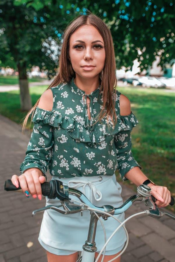 Mooi de zomermeisje in de parktribunes op de fiets Witte fiets van de close-up de groene blouse Emotioneel het kijken en het stel stock afbeeldingen