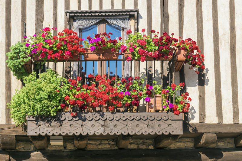 Mooi die balkon met rode geraniums wordt verfraaid stock foto
