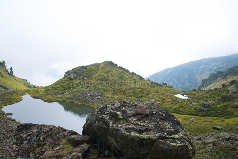 Mooi die bergmeer door indrukwekkende bergen wordt omringd stock afbeelding