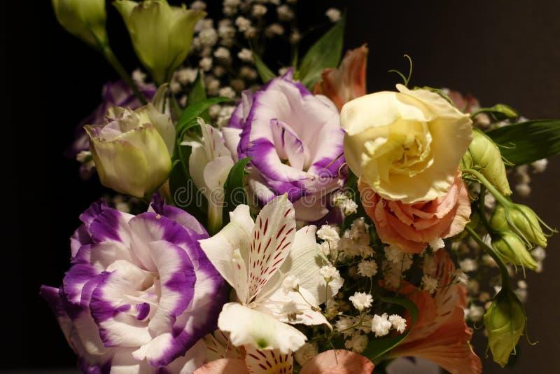 Mooi die huwelijksboeket uit verschillende bloemen op een zwarte achtergrond wordt samengesteld royalty-vrije stock afbeelding