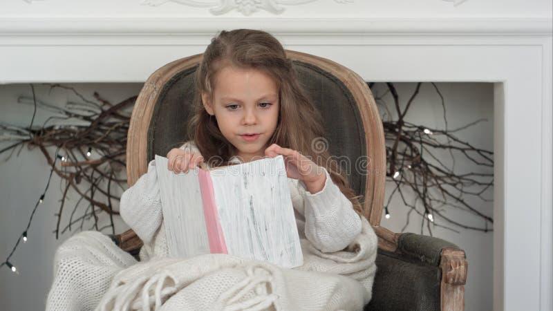 Mooi die meisje in witte Kerstmisdeken wordt verpakt die een boekzitting in een leunstoel lezen dichtbij de verfraaide open haard royalty-vrije stock foto's