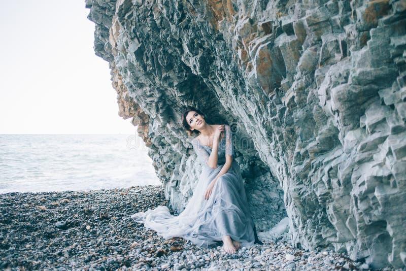 Mooi donkerbruin meisje in blauwe kledingszitting dichtbij rotsen, overzees, die glimlachen, royalty-vrije stock foto